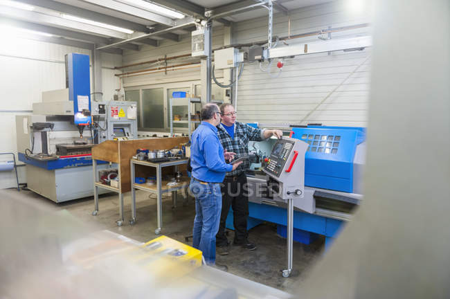 Two men in factory talking at machine for mold making — two people