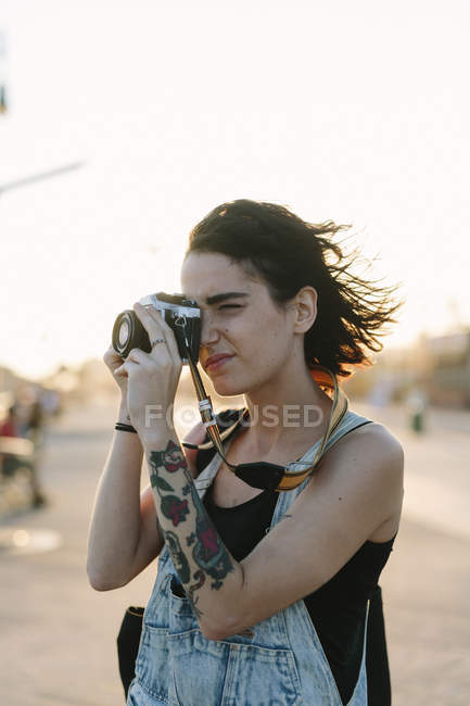 Young woman  taking photos at sunset — Stock Photo