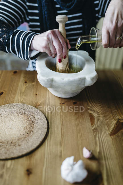 Woman preparing garlic mayonnaise in her kitchen — Stock Photo