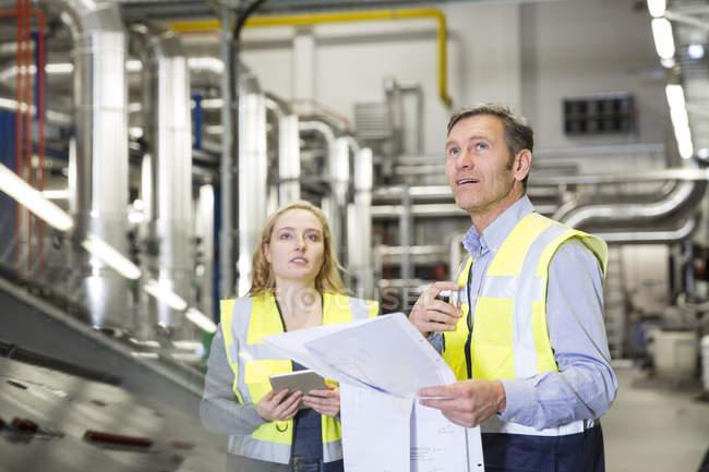 Колеги, носіння світловідбиваючого проведення план в індустріальному — стокове фото