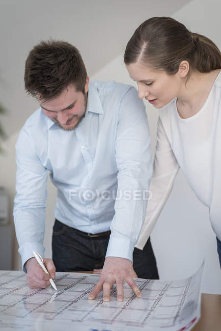 Young man and woman in office looking at calendar — Stock Photo