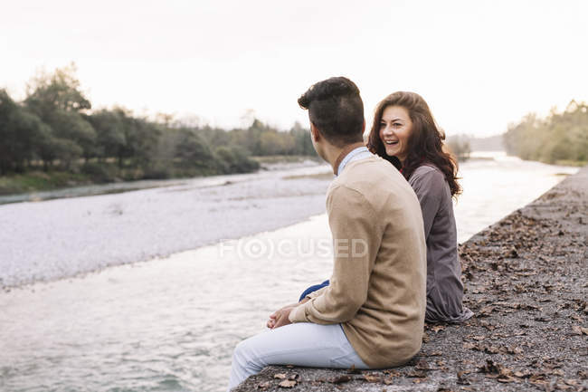 Young couple sitting in front of a river — Stock Photo