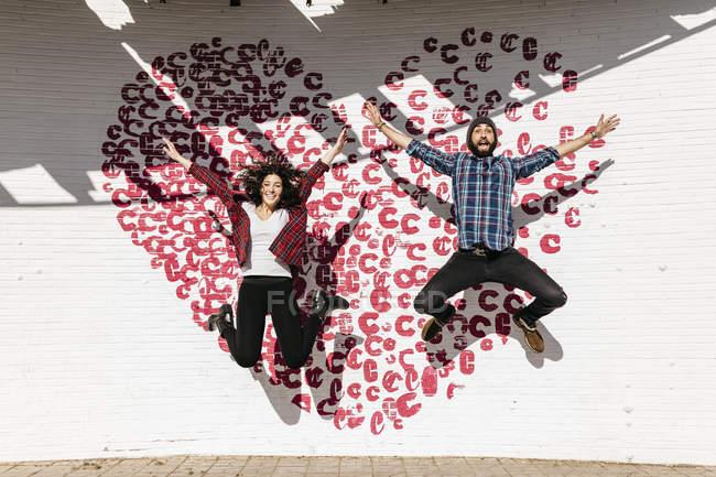 Coppia che salta davanti al cuore dipinto — Foto stock