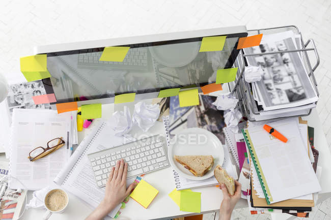 Office wotker at messy office desk eating a sandwich — Stock Photo