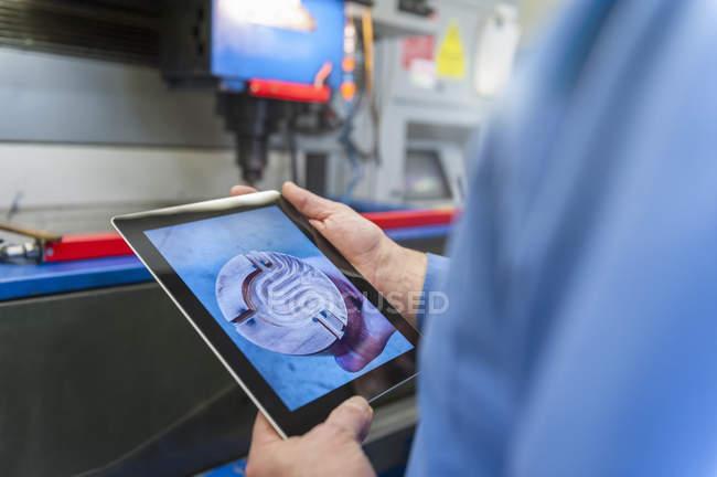 Человек с цифровым планшетом, изучающий металлическую деталь — стоковое фото