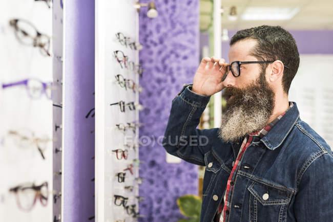 Homme essayant des lunettes en magasin optique — Photo de stock