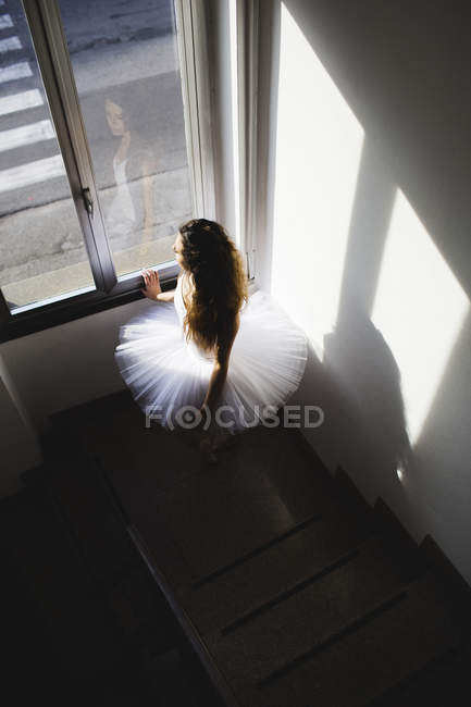 Ballerina in a tutu at the window in hall, overhead — Stock Photo