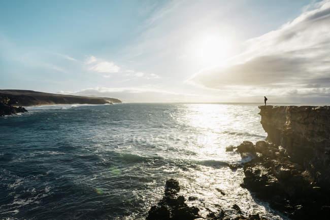 Испания, Канарские острова, Фуэртевентура, Ла Паред, человек, стоящий на утесе на закате — стоковое фото