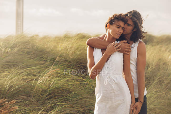 Пара обіймаються на траві — стокове фото