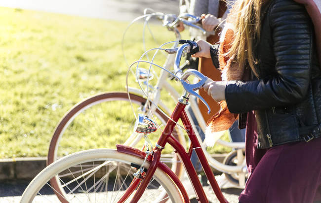 Cropped image of two women strolling with bicycles — Stock Photo