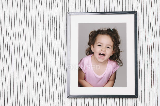 Framed photography of little girl hanging on striped wallpaper — Stock Photo