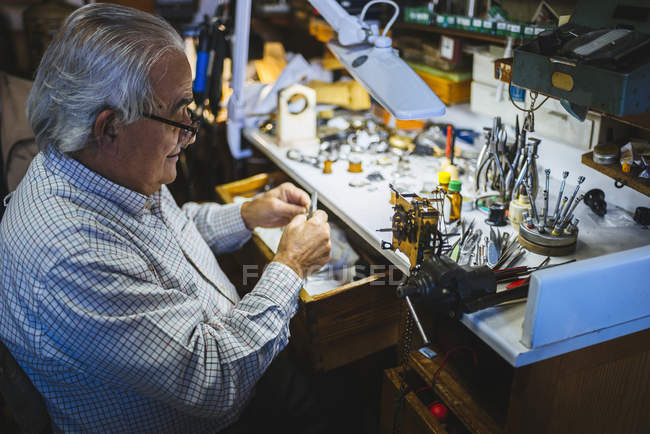 Watchmaker working in watchmaking workshop — Stock Photo