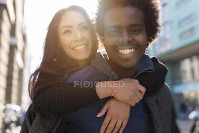 Heureux jeune homme portant petite amie piggyback — Photo de stock