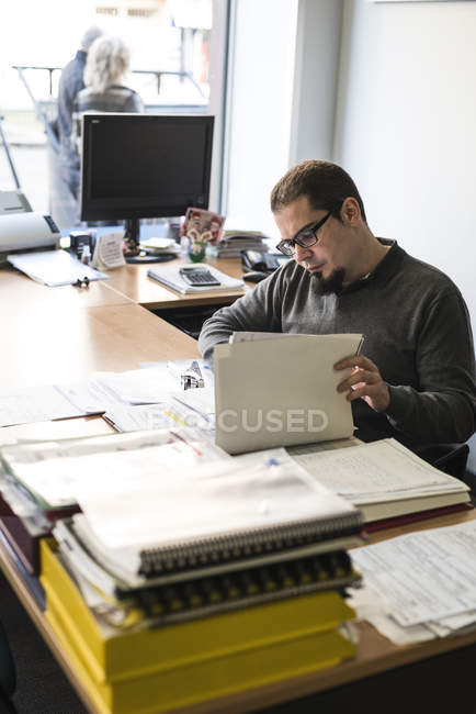 Man doing paperwork at desk in office — Stock Photo