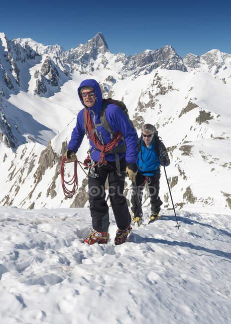 Italie, col du Grand St Bernard, Mont Fourchon, hommes grimpant dans les montagnes enneigées — Photo de stock