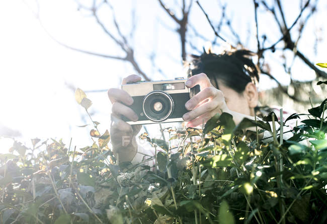 Woman shooting pictures over a hedge with an old camera — Stock Photo