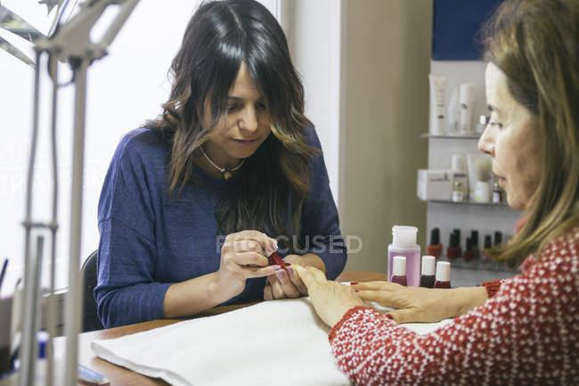 Kosmetikerin trägt Nagellack im Schönheitssalon auf — Stockfoto