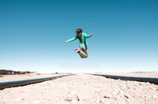 Bolivia, Uyuni tren cementerio, mujer saltando por encima de las vías del tren - foto de stock