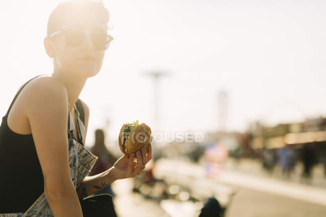Молода жінка, їдять гамбургер — стокове фото