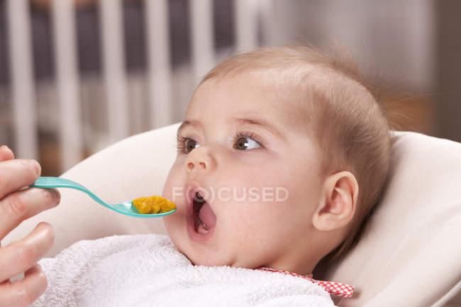Девочка кормится от руки матери — стоковое фото