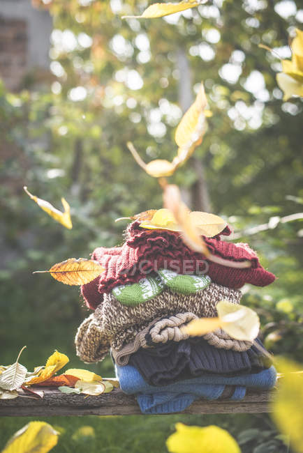 Stack of warm clothing and falling autumnal leaves — Stock Photo
