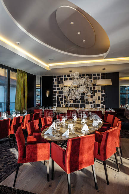 Restaurante con mesa puesto rodeado de sillones rojo - foto de stock