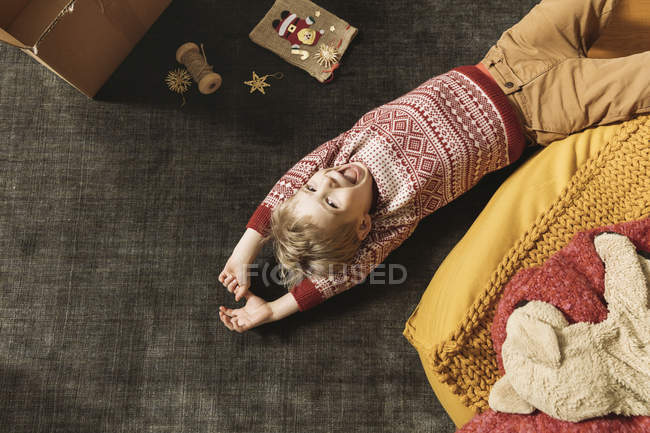Little boy laughing and playing on the carpet next to box of Christmas decoration — Stock Photo