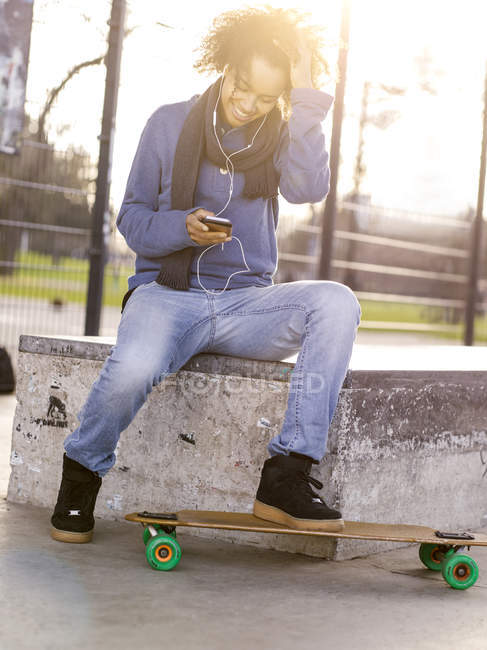 Smiling young woman with longboard hearing music with earphones — Stock Photo