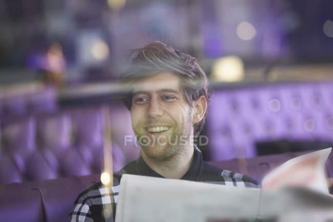 Lächelnde junge Mann sitzt in einer Lounge-Bar mit Zeitung — Stockfoto