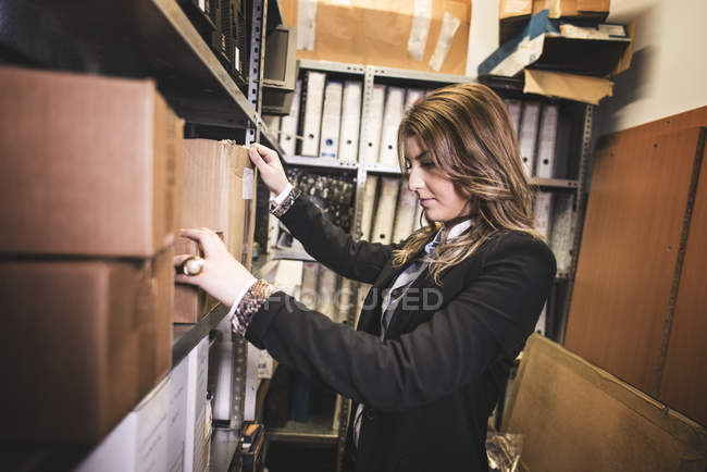 Frau auf der Suche nach Dateien im Büro Keller — Stockfoto