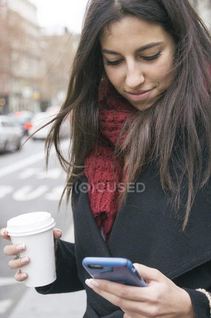 Spain, young woman with coffee to go looking at her smartphone — Stock Photo