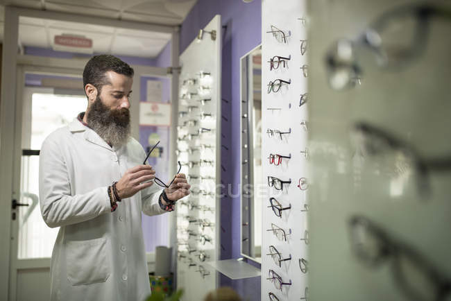 Optometrist checking glasses in store — Stock Photo