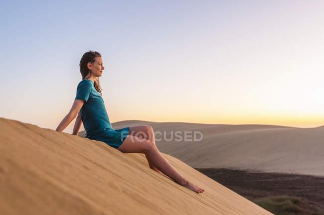 Woman sitting on dune in the desert — Stock Photo