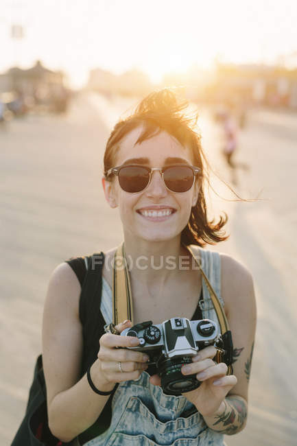 Smiling young woman taking photos at sunset — Stock Photo