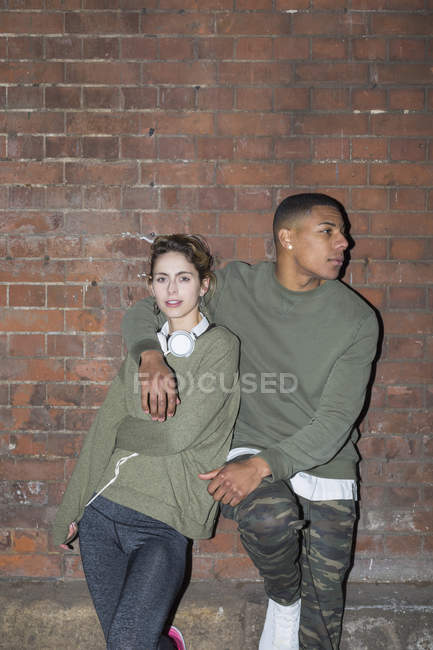 Stylish young couple leaning against brick wall at night — Stock Photo
