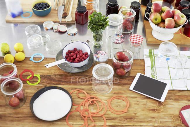 Frutas diferentes e preservantes frascos na cozinha mesa com smartphone — Fotografia de Stock