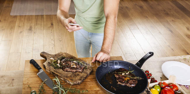 Man with prepared steaks in kitchen using celll phone — Stock Photo