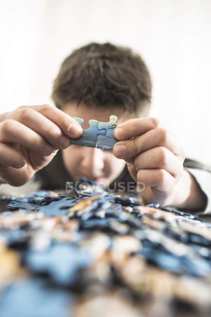 Обрезанное мнение мальчика, холдинг две части головоломки — стоковое фото
