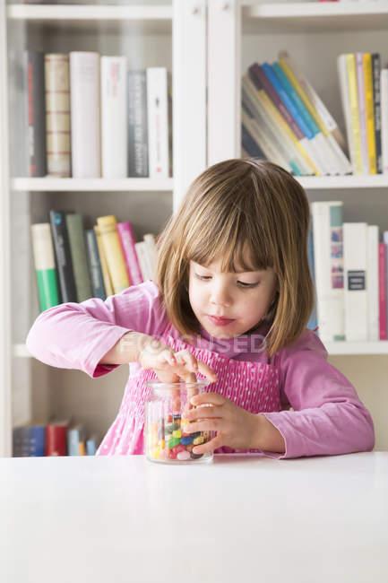 Portrait de jeune fille retire pot de gelée haricot — Photo de stock