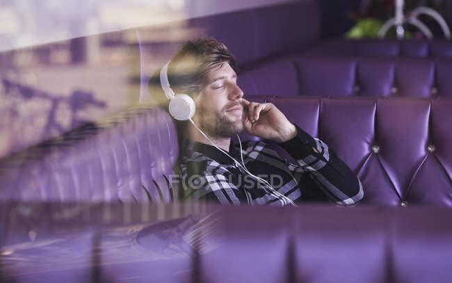Giovane seduto in un lounge bar a sentire musica con le cuffie — Foto stock