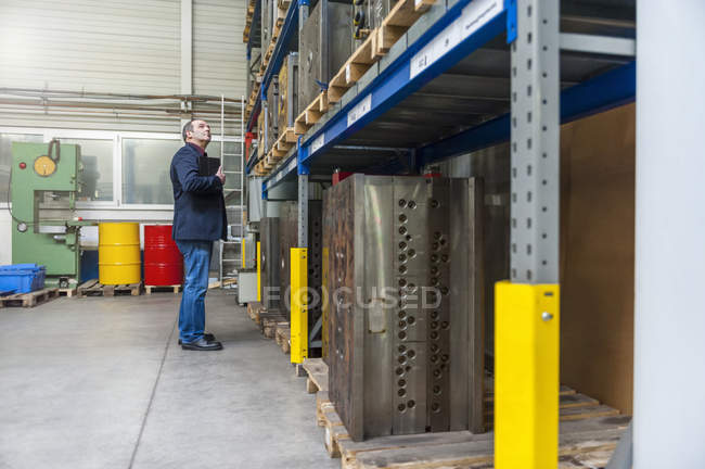 Homme examinant le bloc de la machine dans l'entrepôt — Photo de stock