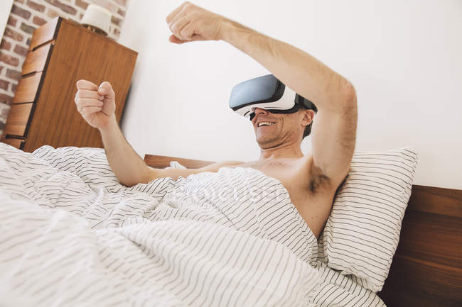 Man in bed wearing virtual reality glasses steering — Stock Photo