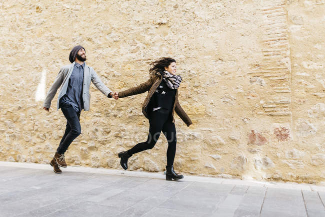 Пара працює перед кам'яною стіною — стокове фото