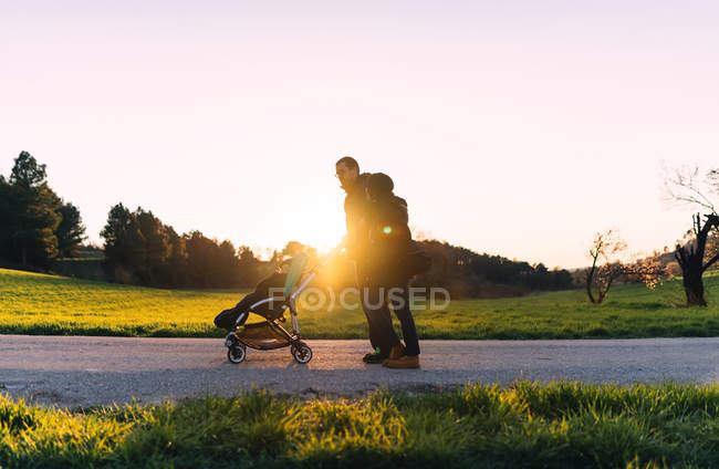 Couple walking with baby in stroller at sunset — Stock Photo