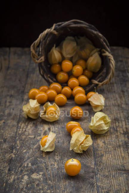 Physalis in cestino di vimini su superficie di legno — Foto stock