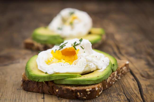 Скибочки хліб з непросіяного борошна з скибочками авокадо і вареними яйцями по дереву — стокове фото
