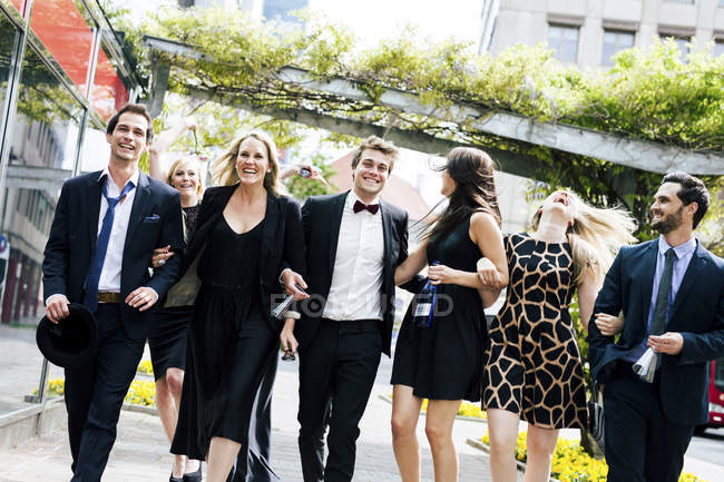 Group of well-dressed happy friends walking outdoors — Stock Photo