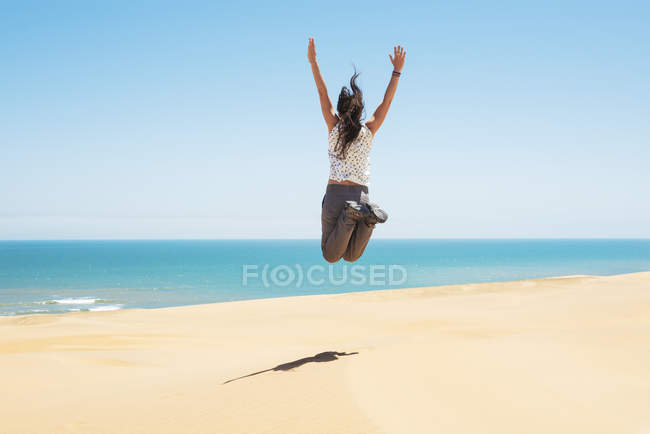 Namibia, Namib desert, Swakopmund, woman jumping in the desert with the sea in the background — Stock Photo