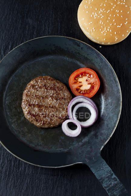 Бургер из жареной говядины с луком и помидорами — стоковое фото