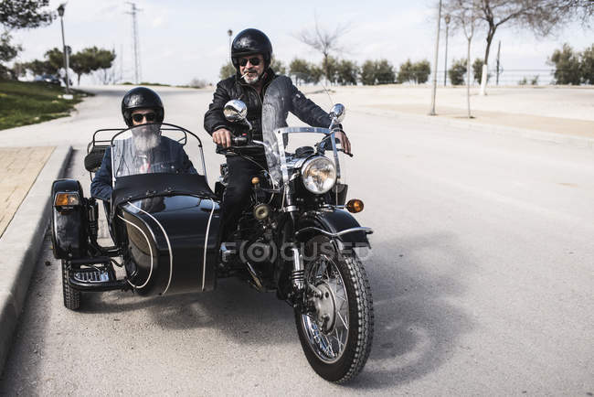 Two bikers standing on a road with sidecar motorcycle — Stock Photo